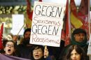 """Women shout slogans and hold up a placard that reads """"Against Sexism - Against Racism"""" as they march through the main railway station of Cologne, Germany, January 5, 2016. About 90 women have reported being robbed, threatened or sexually molested at the New Year's celebrations outside Cologne's cathedral by young, mostly drunk, men, police said on Tuesday.   REUTERS/Wolfgang Rattay - RTX215NV"""
