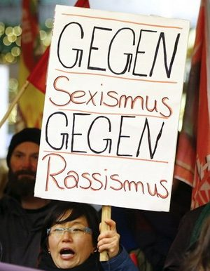 "Women shout slogans and hold up a placard that reads ""Against Sexism - Against Racism"" as they march through the main railway station of Cologne, Germany, January 5, 2016. About 90 women have reported being robbed, threatened or sexually molested at the New Year's celebrations outside Cologne's cathedral by young, mostly drunk, men, police said on Tuesday.   REUTERS/Wolfgang Rattay - RTX215NV"